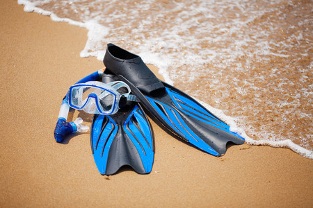 swim mask: Swim flippers, mask, snorkel in the surf on the sandy beach; selective focus