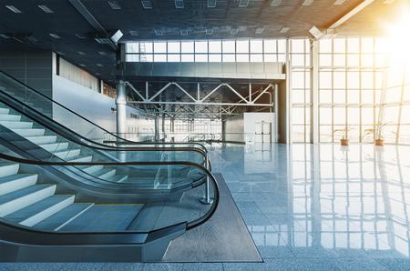 Las escaleras mecánicas y escaleras en el vestíbulo del moderno edificio de oficinas, centro comercial del aeropuerto o de compras, paredes de vidrio y el piso de reflexión, la luz natural y los brillos