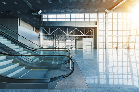 Escalators and stairs in lobby of modern office building, airport or shopping mall, glass walls and reflective floor, natural light and flare