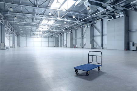 warehouse equipment: Interior of empty warehouse with a cart Stock Photo
