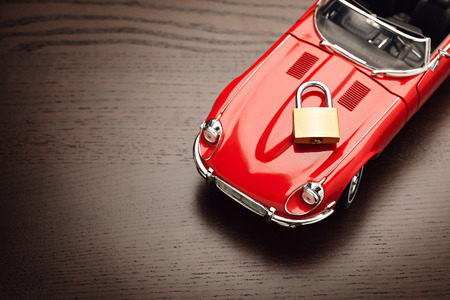 surface view: Model of a red car with padlock on wooden surface, view from above. Concept of security. Close up, copy space. Stock Photo