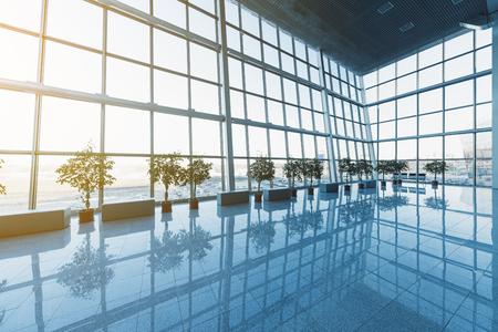 Innenansicht der modernen Lobby, Terminal oder Warteraum mit Glaswänden und reflektierenden Boden, natürliches Licht und Fackel Standard-Bild
