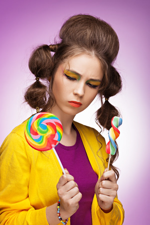 what to eat: Young beautiful woman choosing what colorful lollipop to eat Stock Photo