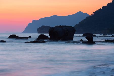 Dramatic coastal sunset on rocky beach; low shutter speed