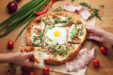 tomando refresco: Hands taking slices of delicious pizza served on wooden table surrounded with fresh ingredients Foto de archivo