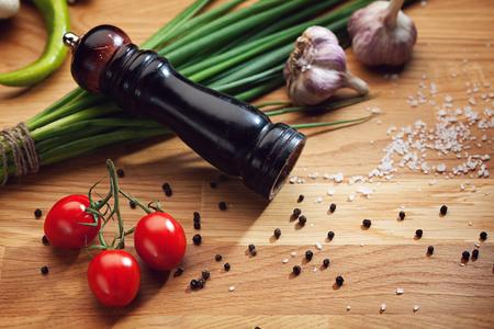 Stilleven met pepermolen en peperkorrels, zout, tomaten, knoflook en groene ui Stockfoto