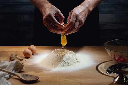 Cook hands kneading dough, cracking an egg in flour. Low key shot, close up on hands, some ingredients around on table. Stockfoto