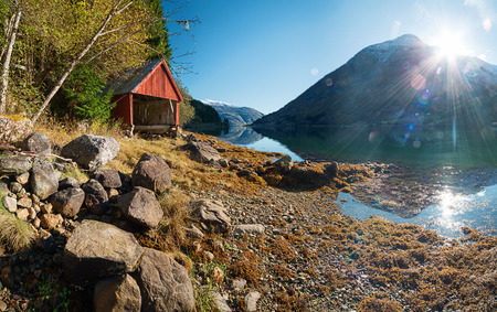 Norwegian landscape with fjord, mountains and traditional wooden boat storage on shore