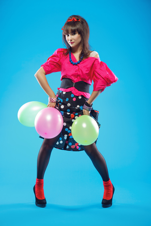 Young woman wearing colorful old-fashion clothes in pinup style. Also she can represent a member of a youth counterculture Stilyagi existed from the late 1940s until the early 1960s in the Soviet Union