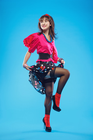 Young woman in colorful old-fashion clothes in pinup style dancing. Also she can represent a member of a youth counterculture Stilyagi existed from the late 1940s until the early 1960s in the Soviet Union Stock Photo