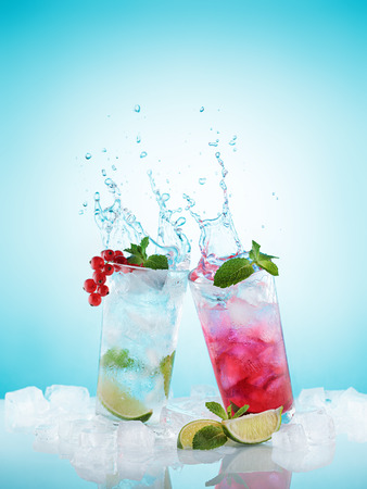 Homemade lemonades in misted glasses splashing out over light blue background. Refreshing cold summer drink