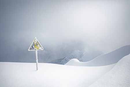Yellow warning sign covered with snow on the edge of the ski slope, snow blizzard on background Stock Photo
