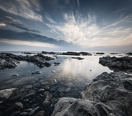 Long exposure landscape with the rocky coast of Black sea at the end of the day. Cloundscape over the calm water and grey dramatic rocks.