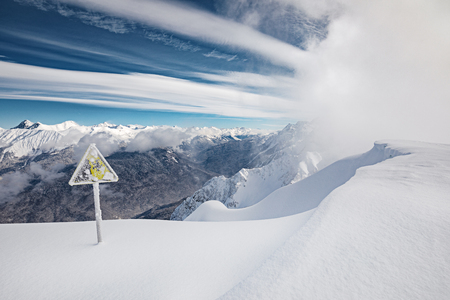 Yellow danger sign, winter mountains, blue sky and snow blizzard coming on background Stock Photo