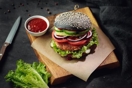 Vegeterian soy burger on black bun with fresh vegetables served with ketchup on dark background