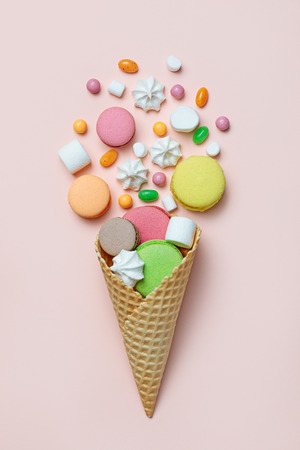 Top view of sweets spilling out of waffle cone on pastel pink background, flat lay