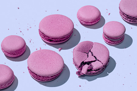 Delicious lavender macarons on pastel blue background with shadows