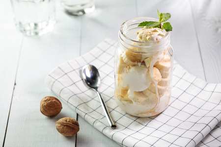 Banana split with vegan ice cream served in glass jar