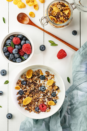 Flat lay with light healthy breakfast with cereal and berries on white wooden table Imagens