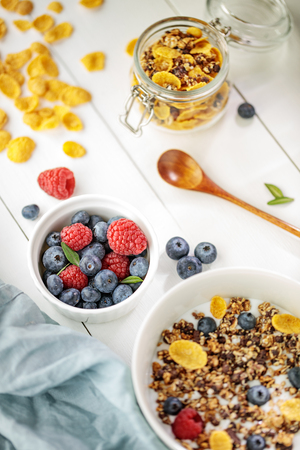 Light healthy breakfast with cereal and berries on the white wooden table, selective focus