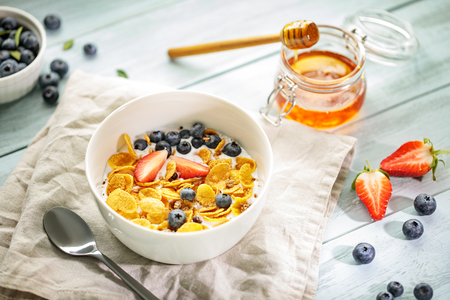 Light healthy breakfast with corn flakes, berries and honey on white wooden table