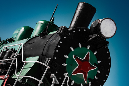 Black cabin of old soviet steam locomotive with red star, close up, dramatic and contrast