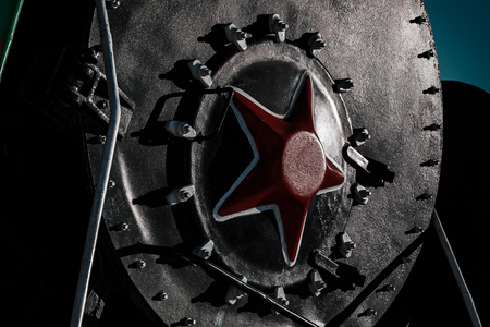 Front red star on black cabin of old soviet steam locomotive, close up, dramatic light