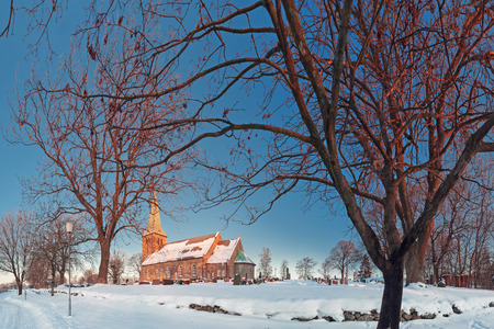 Winter panoramic landscape with a norwegian countryside church and graveyard at sunset Stockfoto