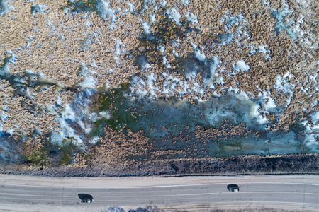 Aerial drone view of a highway passing through swampland at winter, Moscow region, Russia