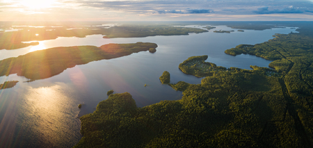 Aerial panoramic view of Suoyarvi lake at sunset surrounded by forests of Karelia, Russia