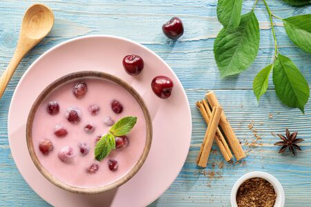 Flat lay of meglevesh, hungarian cold cherry soup, served in wooden bowl