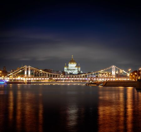 Night view at the main Russian Cathedral of Christ the Savior and the Krymsky Bridge from the embankment of Gorky Park, Moscow, Russia Фото со стока
