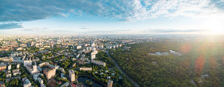 Aerial view of Moscow over the Sokolniki district at summer sunset. There are the Sokolniki park and distant Ostankino tower and Moscow City business center skyscrapers Imagens