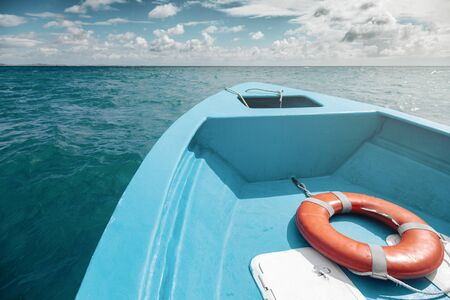 View of the front of a blue boat with an orange lifebuoy, turquoise waters and distant coast are ahead Фото со стока