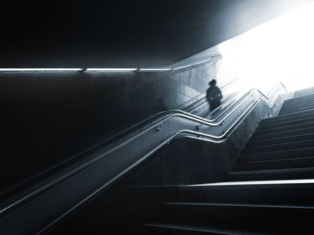 Someone on escalator is moving up to bright daylight from darkness and electric light of underground, motion blur and flares, monochrome image 免版税图像