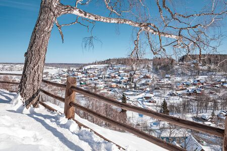 Town of Plyos on the banks of the Volga river, Russia. Winter view from the Cathedral Mountain, birch tree on foreground