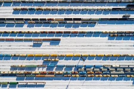 Top aerial view of many colorful freight trains on the parallel railroad tracks at winter, industrial concept 写真素材