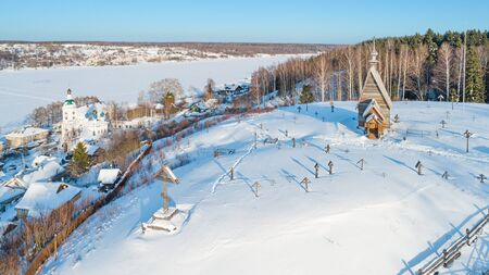 Town of Plyos on the banks of the Volga river, Russia. Aerial winter view on the wooden Church of the Resurrection and the old cemetery around it.