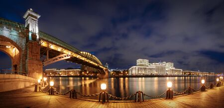 Panorama of the main building of the Ministry of Defence of the Russian Federation and Pushkinsky (Andreevsky) over Moskva-river illuminated at night, Moscow, Russia