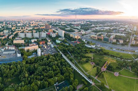 Aerial view of Moscow over the Rostokino Aqueduct (Millionny Bridge) and the park around it at summer sunset. There are distant VDNKh park, Ostankino tower and Moscow City business center skyscrapers