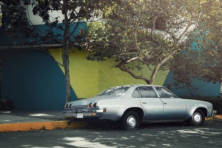 Silver old classic car parked on the side of the street next to painted wall, Coyoacan, Mexico City