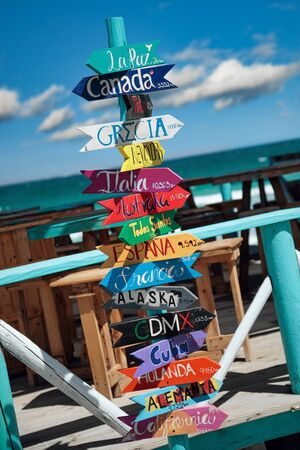 Colorful wooden direction signpost with destination countries at Playa El Tecolote near La Paz, Mexico