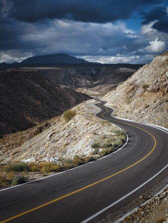 Dramatic cloudscape over empty road through scenic canyon, Santa Rosalia, Baja California, Mexico Фото со стока
