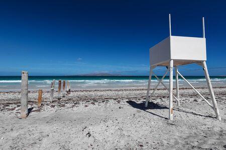 Beach landscape with white lifeguard post facing the sea, vivd blue sky and grey sand of Playa El Tecolote near La Paz, Mexico