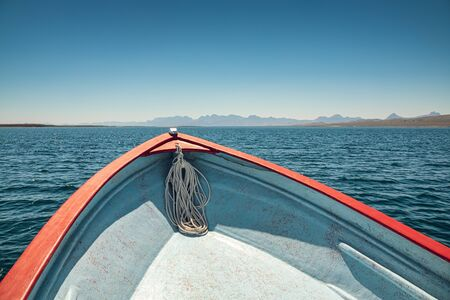 View of the front of a boat at the calm sea -sunny weather, turquoise waters and distant coast are ahead
