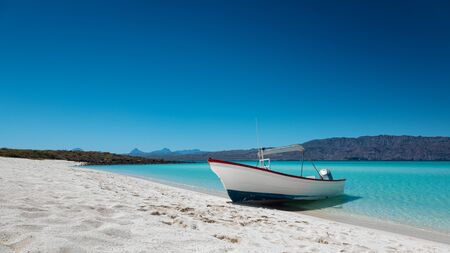Motor boat at the paradise beach with white sand, turquoise sea and blue sky, Playa Isla Coronado, Mexico