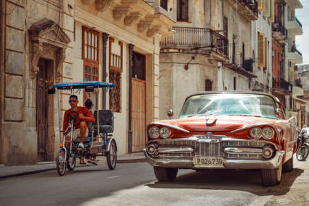 Havana, Cuba - March 22, 2019: Shiny retro car parked on the street and bicycle taxi driver riding by 新闻类图片