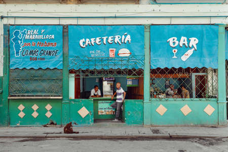 Havana, Cuba - March 22, 2019: Blue and green facade of a small cafe bar, locals are chilling inside