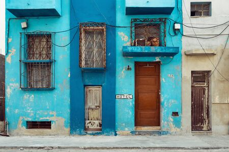 Rough painted facades of buildings with bars on the windows, Havana, Cuba
