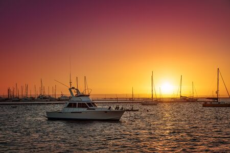 Marina at sunset, one small white yacht on foreground, La Paz, Mexico 免版税图像